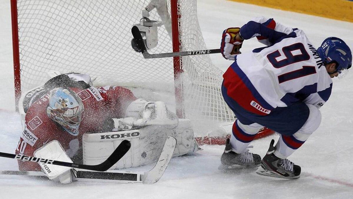 Slovakia's Michel Miklik (R) tries to score past Switzerland's goalkeeper Reto Berra during their 2012 IIHF men's ice hockey World Championship game in Helsinki.