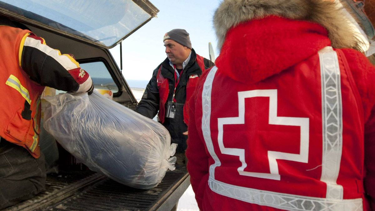Red Cross workers load sleeping bags into the back of a pick up truck after a shipment of winter supplies arrived by plane the remote Norther Ontario native reserve of Attawapiskat on Nov. 29, 2011.