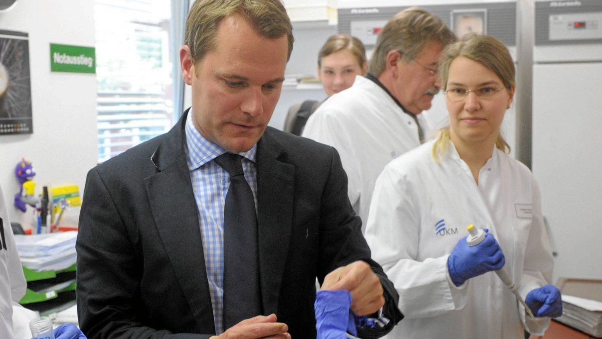 "German Health Minister Daniel Bahr puts on protective gloves as he visits a lab in the western German city of Muenster on June 18, 2011. The Environment Ministry of the state of Hesse announced that the deadly O 104:H 4 strain of the deadly E. coli bacteria had been found in the ""Erlenbach"" stream near Frankfurt am Main."