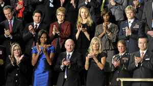 First lady Michelle Obama and guests applaud during President Barack Obama's State of the Union address on Capitol Hill in Washington, Tuesday, Jan. 24, 2012. Front row, from left are, Jackie Bray, Obama, retired Capt. Mark Kelly, Jill Biden, Sgt. Ashleigh Berg, Hiroyuki Fujita, Richard Cordray, and Sara Ferguson. Second row, from left are, Eric Schneiderman, Juan Jose Redin, Debbie Bosanek, Laurene Powell Jobs, Alicia Boler-Davis, and Col. Ginger Wallace. (AP Photo/Susan Walsh)