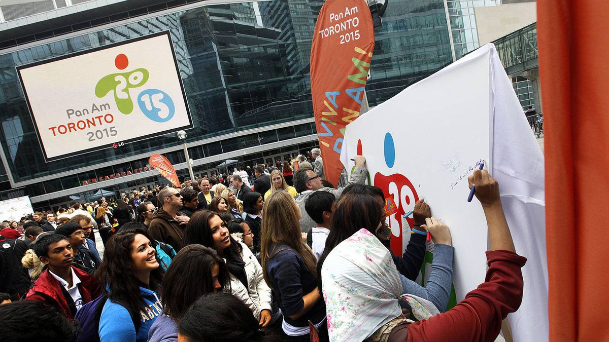 A crowd of people sign a mural with the new logo on it during the official launch of the 2015 Pan/Parapan American Games where a street party which was held at Maple Leaf Square in Toronto, Ontario, Canada.