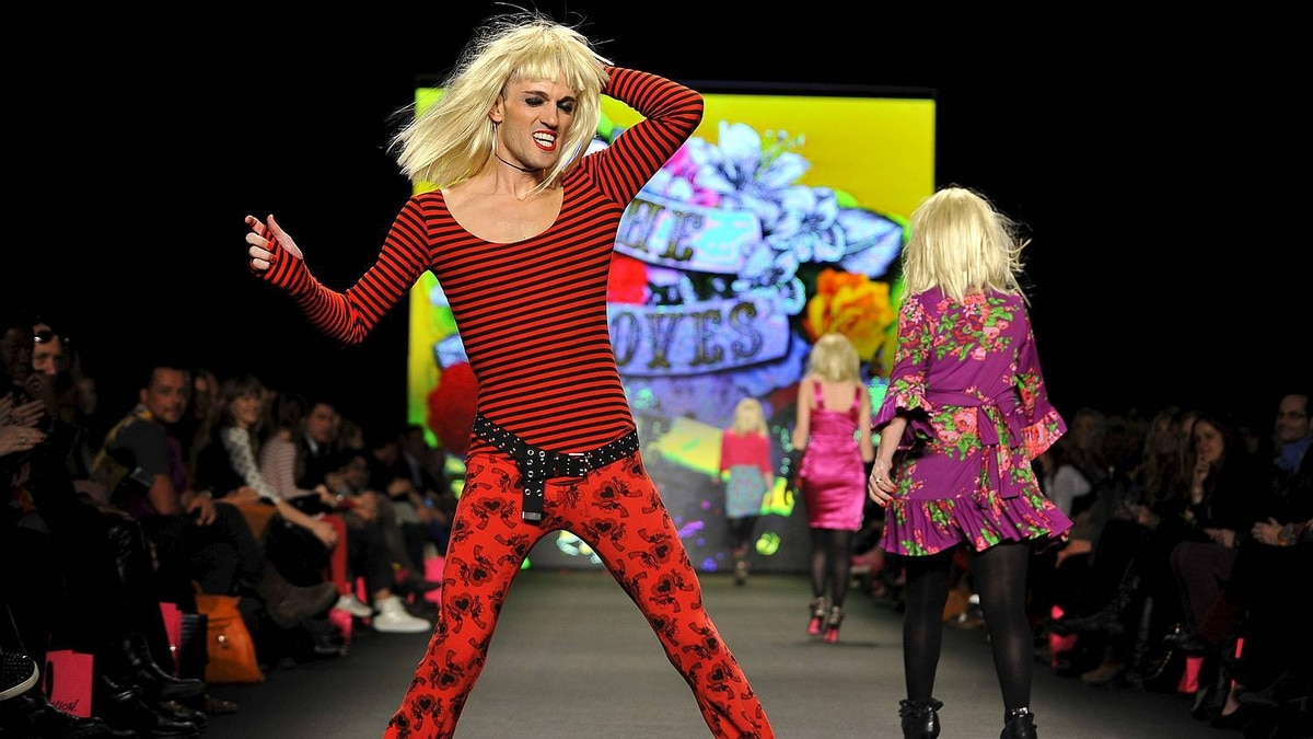 A man wearing a Betsey Johnson wig dances on the runway after Betsey Johnson's Fall 2011 fashion show during Fashion Week on Monday, Feb. 14, 2011, in New York.