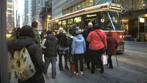 As the afternoon rush hour home begins on Nov 24 2010, commuters wait to board an eastbound King streetcar at Yonge St. in downtownToronto.