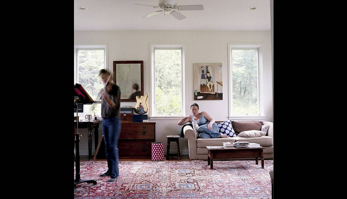 Self portrait of photographer Tanja Alexia Hollander for the portraits of friends on facebook story. Photo was taken in West Cornwall, Vermont, at the home of one of�Ćthe Facebook friends she shot --on left is Emily Sunderman, playing violin.