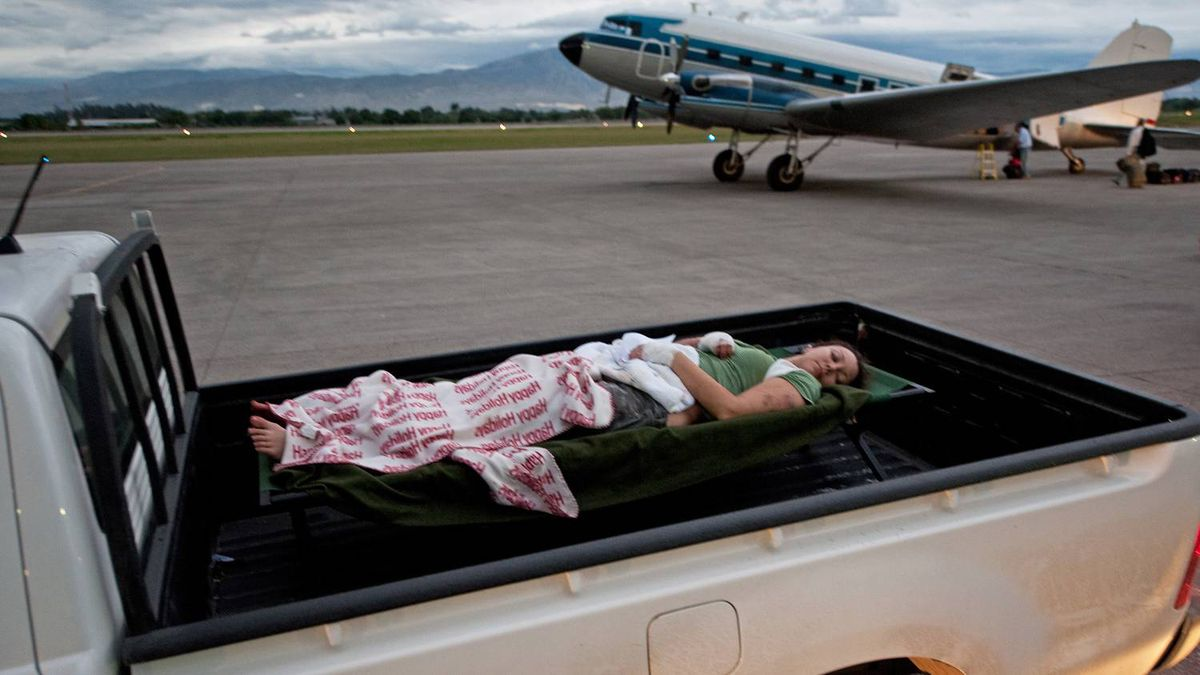 An unidentified female earthquake victim is transported by pickup truck to the airport in Port-Au-Prince from where she will be evacuated for treatment in another country. Paul J. Richards/AFP/Getty Images
