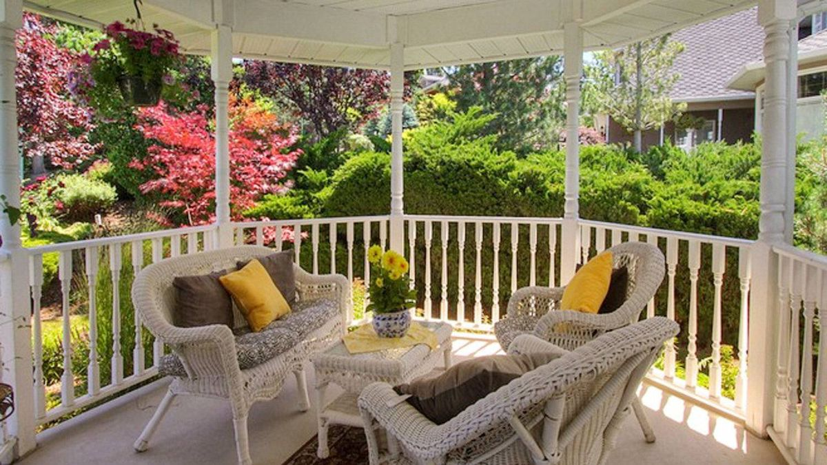 A covered veranda patio offers views of the manicured backyard.