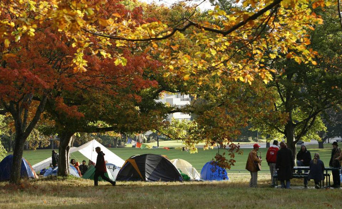 """Supporters join David Arthur Johnston at their erected """"Tent City"""" in Beacon Hill Park at sunrise in Victoria Friday."""