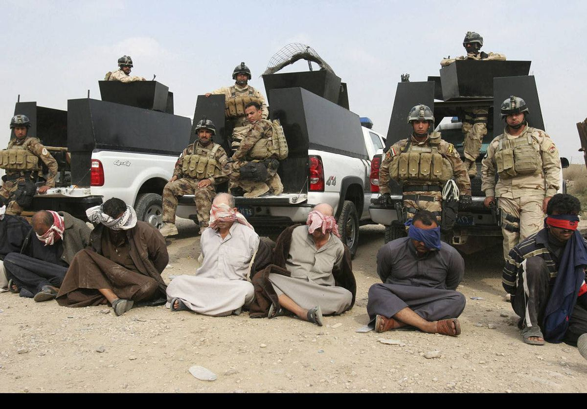 Suspected members of al-Qaida are seen blindfolded and handcuffed in Jurf al-Sakhar, Iraq. Special operations commandos arrested nine people during recent operations.