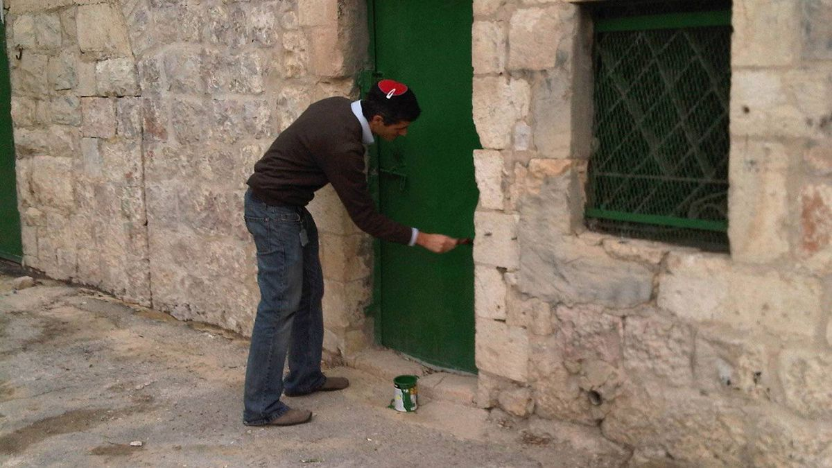 Avi Mayer cleans the graffiti off the Nebi Akasha mosque after it was apparently attacked by young Israeli settlers.