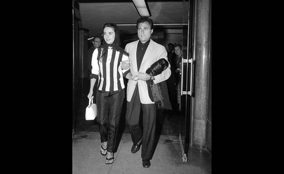 Elizabeth Taylor is escorted from Cedars of Lebanon Hospital by her husband, producer Mike Todd, Dec. 22, 1957. She had been hospitalized for appendicitis.