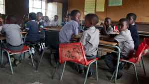 Grade 1 students at Kholwane primary school in rural Swaziland sit in groups of seven at desks intended to seat two. The school has a shortage of desks, and broken chairs, but no budget for new ones. The school was forced to close early for the year because it had run out of food and water, a result of the country's financial crisis.