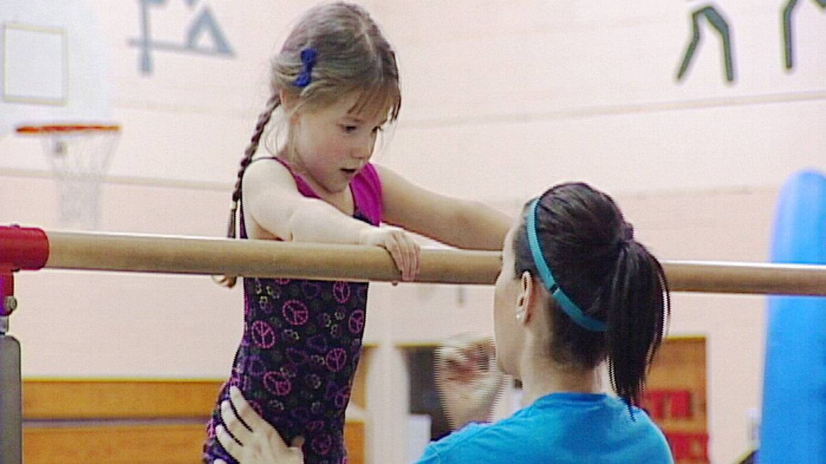 Coach assists child about to swing from the high bar.