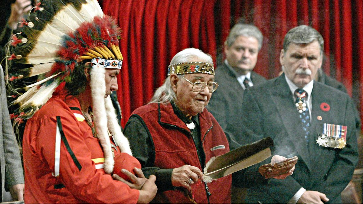 William Commanda burns sweetgrass during a 2005 ceremony in the Senate chamber watched by elder Dominique Rankin, left, and General Romeo D'Allaire.