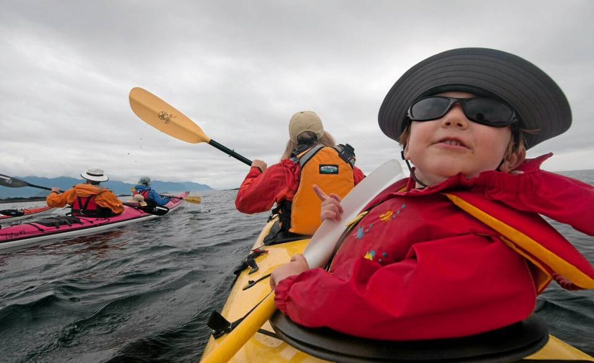 Seated behind his mother Christine, three-year-old Bodi peers back to watch a passing sea otter. Dave Pinel, owner of West Coast Expeditions, is in the pink kayak beside, with his two year old son Morgan, and Bodi's grandmother Isabelle up front.
