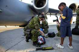 A boy sucks his thumb as Master Corporal Lola Lagler, of the Canadian Forces, searches his bag before boarding a transport plane in Port-au-Prince, Monday, Jan. 18, 2010.