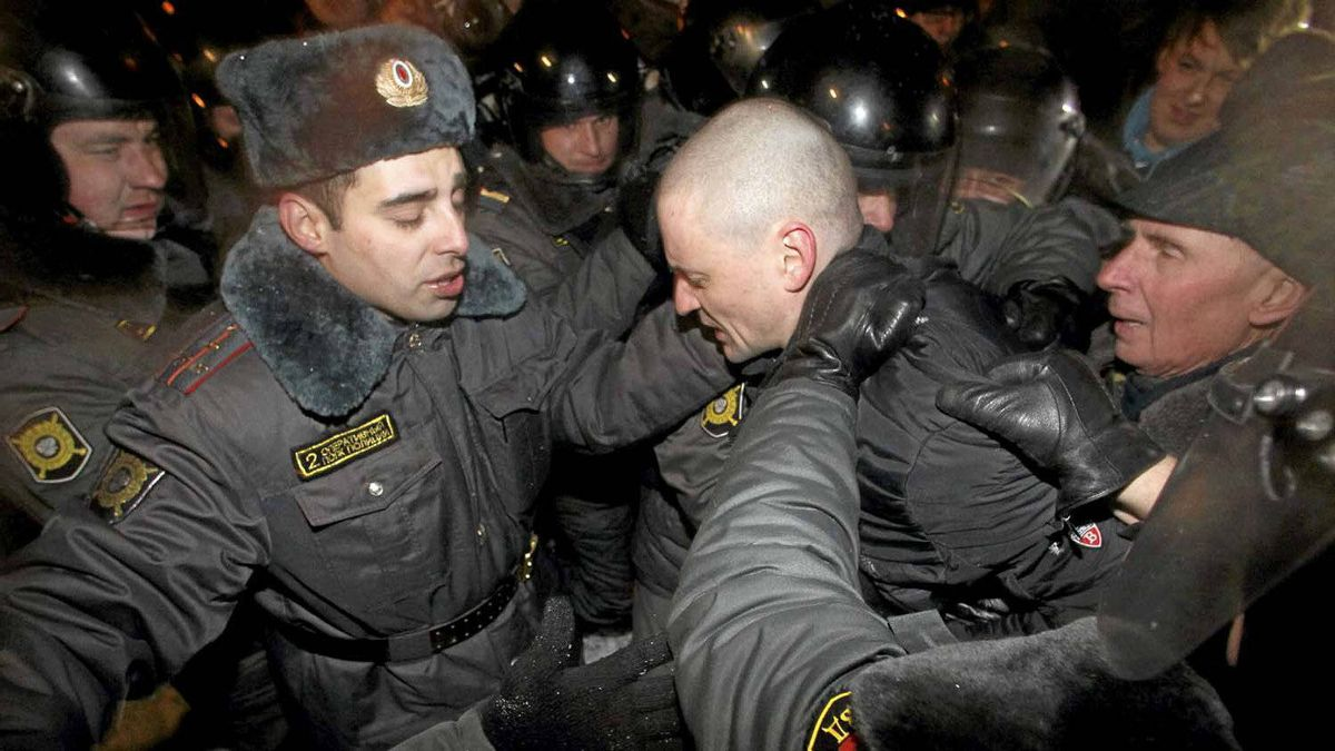 """Opposition leader Sergei Udaltsov (centre) is detained by police. Thousands of protesters chanting """"Russia without Putin"""" took to the streets of Moscow and St. Petersburg to challenge Vladimir Putin's victory."""