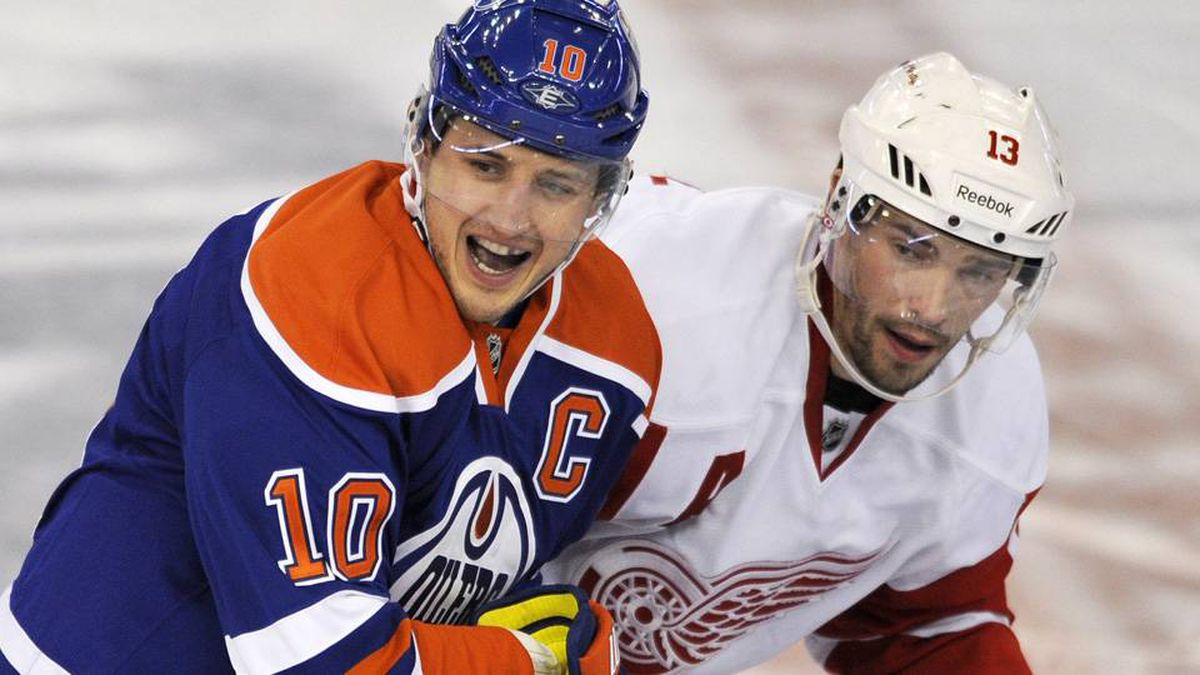 Edmonton Oilers' Shawn Horcoff, left, calls for the puck while being checked by Detroit Red Wings' Pavel Datsyuk during the second period of their NHL hockey game in Edmonton.