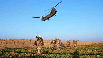 Canadian troops, belonging to November Company of the 3rd Battalion Royal Canadian Regiment make their across a field as a Canadian CH-47D Chinook lifts off after dropping them off during an assault Saturday, March 7, 2009 on a Taliban command centre in Zhari District. It was the first time Canadian soldiers had conducted a combat assault with their own aircraft, rather than relying on other countries.