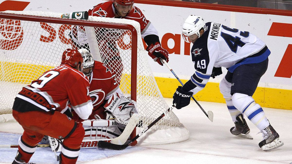 Winnipeg Jets forward Ben Maxwell (49) attempts to jam it past Carolina Hurricanes goalie Brian Boucher (33) as Jiri Tlusty (19) and Tim Brent (37) watch for the rebound during second period pre-season NHL action in Winnipeg on Wednesday, September 28, 2011.