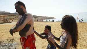 A boy smears black mud on his relative on a beach near the Dead Sea.