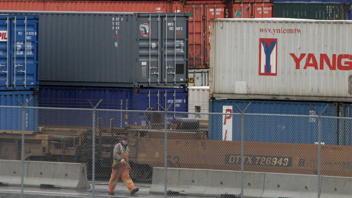 A workers passes cargo containers stacked up at the Port of Vancouver in Vancouver, B.C., in this file photo.