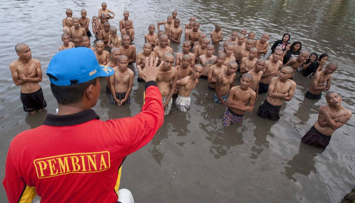 A police officer gives instruction to a group of detained Indonesian punks in a lake after their hair was shaved off at a police school in Aceh Besar in Aceh province.