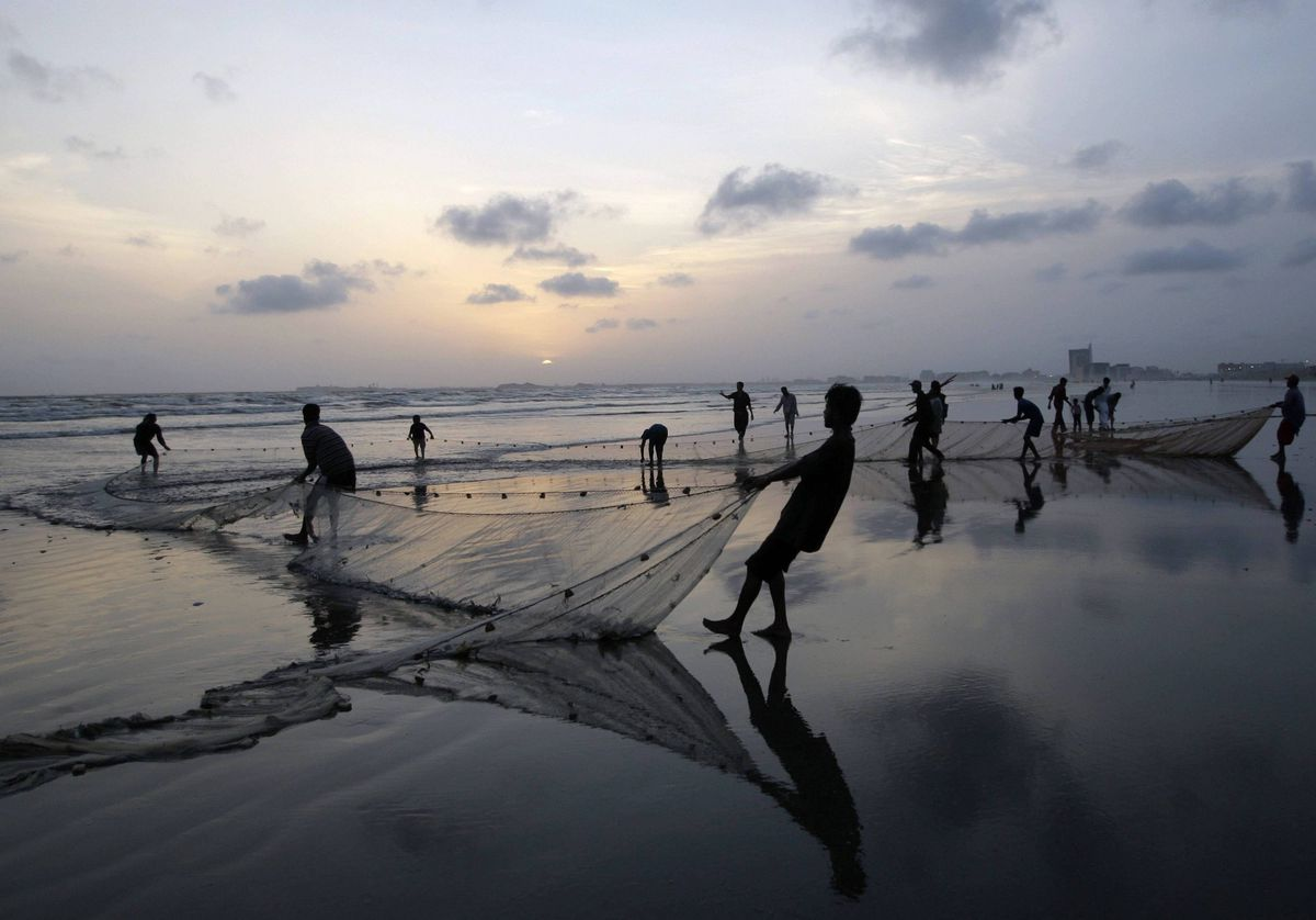 Pakistani fishermen pull their net out of the sea onto the beach in Karachi, Pakistan.