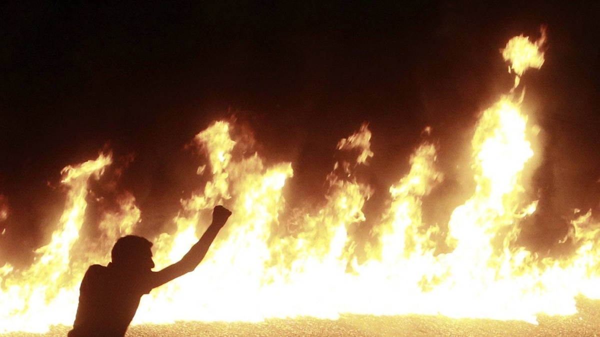 A protester stands near a line of fire during a demonstration in Cairo October 9, 2011. Nineteen people were killed in Cairo on Sunday when Christians, some carrying crosses and pictures of Jesus, clashed with military police.