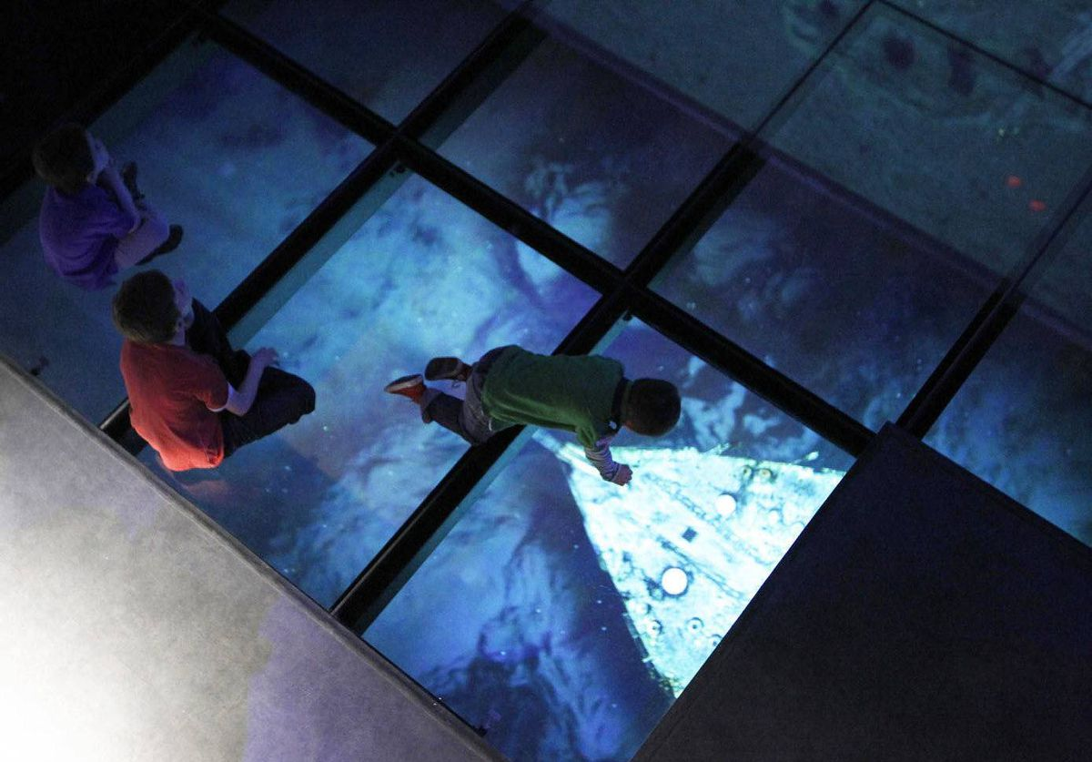 Boys sit and crawl over glass tiles in the cinema room of the Titanic Belfast building in Belfast, Northern Ireland. The building, which opens in April, will tell the story of the Titanic from the ship's construction in Belfast to her sinking.