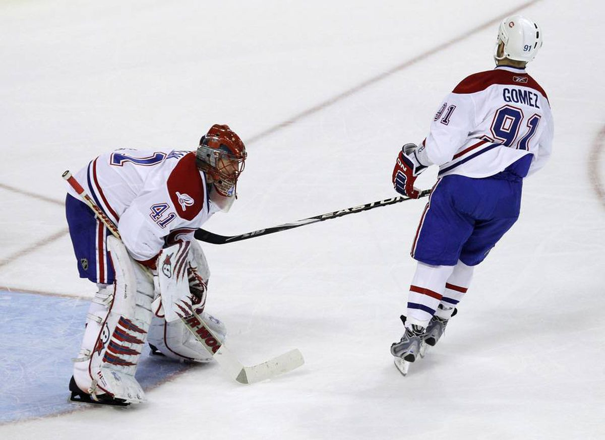 Montreal Canadiens goalie Jaroslav Halak is consoled by Scott Gomez after a Philadelphia Flyers' goal during the third period of Game 2.