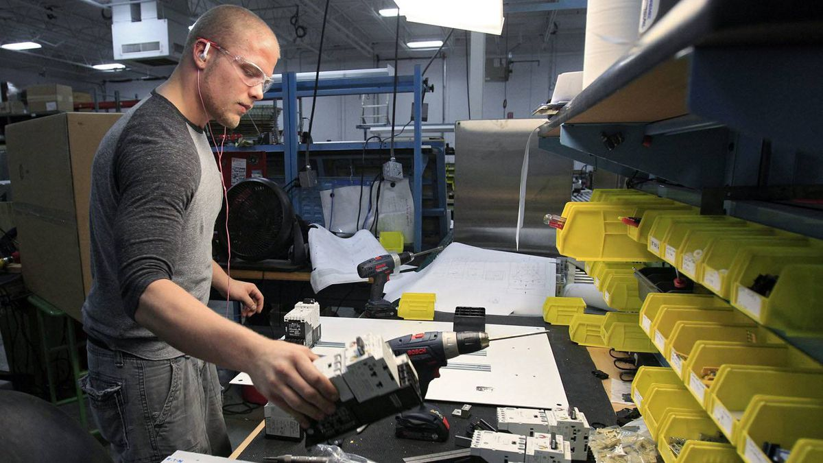 In this photo made April 20, 2012 Sean Stigall attaches circuit breakers to a panel at the Eaton Corp. electrical division in Parma, Ohio.