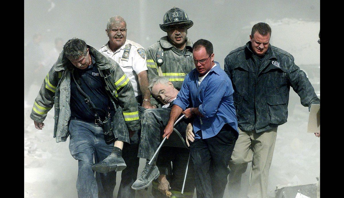 Rescue worker remove fatally injured New York City Fire Department chaplain Rev. Mychal Judge from one of the World Trade Center towers in New York City, early September 11, 2001.