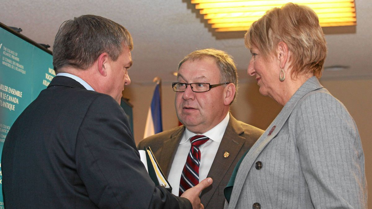 New Brunswick Premier David Alward speaks with Nova Scotia Premier Darrell Dexter (centre) and Newfoundland and Labrador Premier Kathy Dunderdale at the 20th session of the Council of Atlantic Premiers in St. John's, N.L. on Monday Dec. 5, 2011.