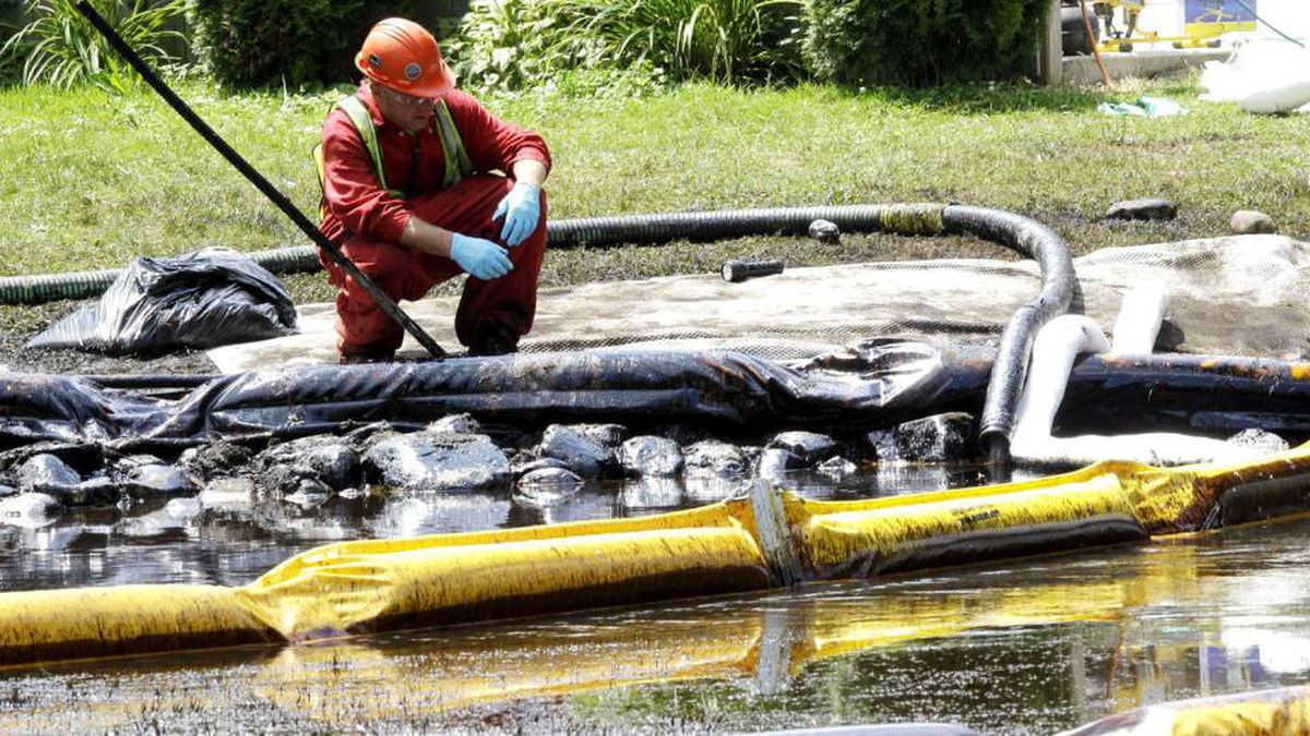 A worker monitors water in Talmadge Creek in Marshall Township, Mich., near the Kalamazoo River as oil from a ruptured pipeline, owned by Enbridge Inc, is attempted to be trapped by booms Thursday, July 29, 2010.