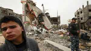 A Hamas policeman (R) stands guard next to a destroyed building after an Israeli air strike in Jabalya in the northern Gaza Strip March 12, 2012. Israeli air strikes killed two Palestinian militants and wounded 25 civilians in the Gaza Strip on Monday, medical sources said, as cross-border hostilities continued into a fourth day.