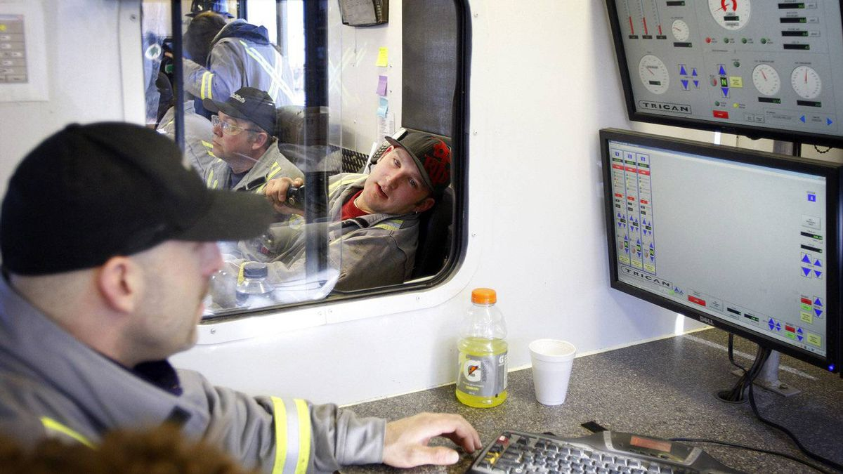 Trican Well Service employees monitor the hydraulic fracturing process from an onsite control centre near Bowden, Alta.