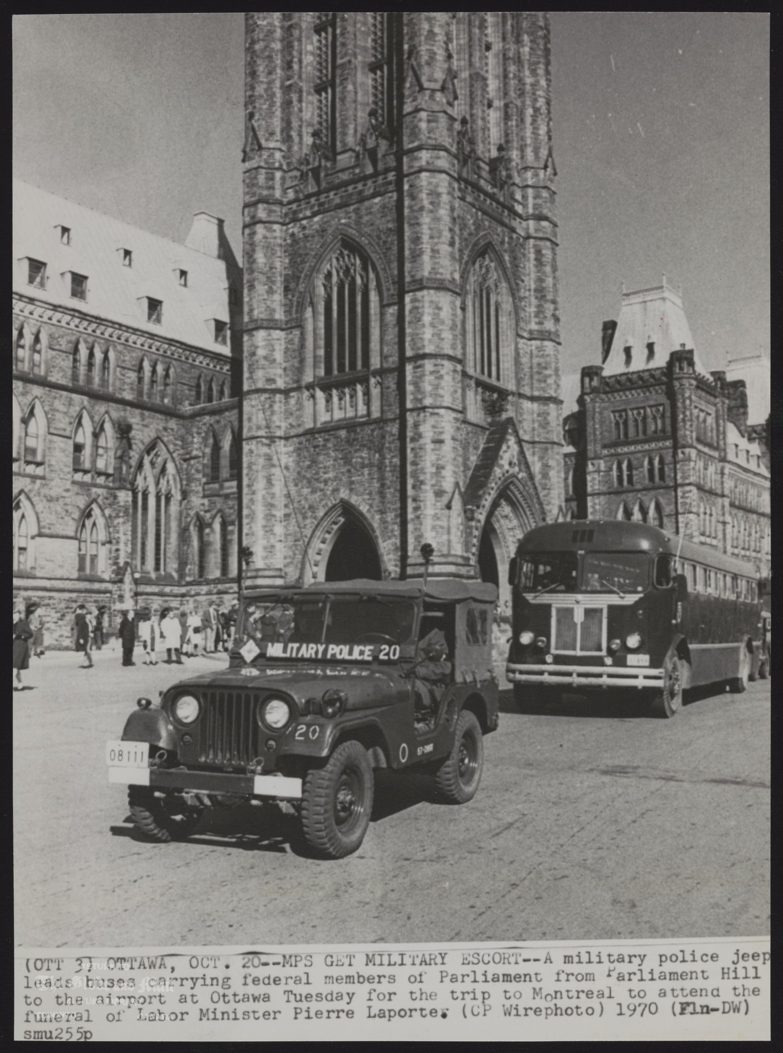 The notes transcribed from the back of this photograph are as follows: CANADA Security (OTT 51 0TTAWI7~0CT. 20--MPS GET MILITARY ESCORT—A military police jeep leads buses carrying federal members of Parliament from Parliament Hill to the airport at Ottawa Tuesday for the trip to Montreal to attend the funeral of Labor Minister Pierre Laporte. (CP Wirephoto) 1970 (Fln-DW) smu 255p