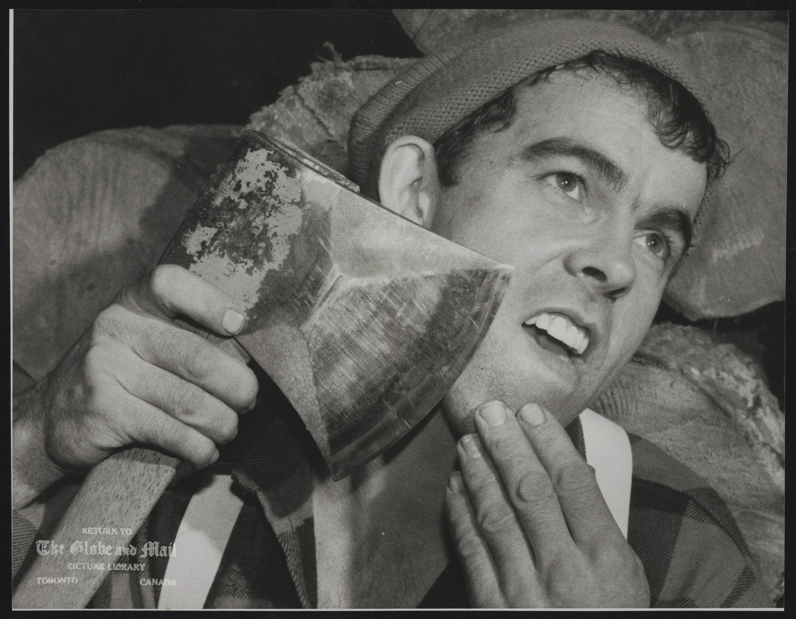 The notes transcribed from the back of this photograph are as follows: CANADIAN NATIONAL (Toronto) Karl Bischoff of Celista, B.C. says his axe is so sharp that he can shave with it. He is in Toronto for the Sportsmen's Show at Exhibition Place. The show ends March 19/89