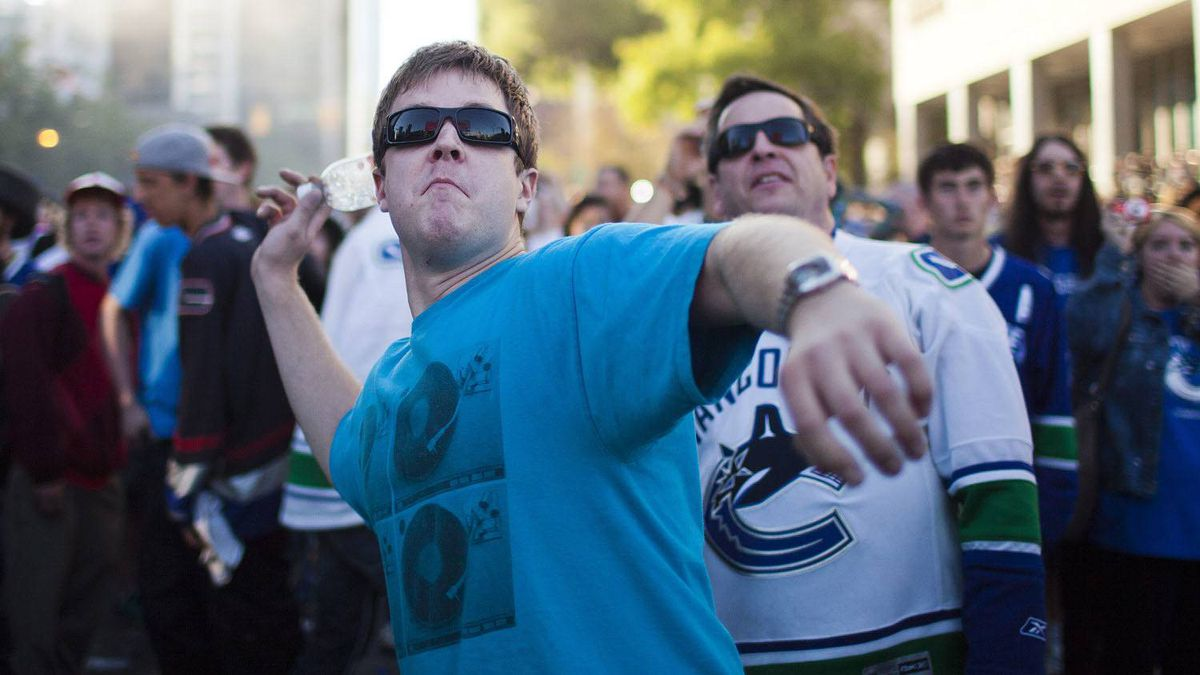 A Canucks fan throws a bottle at a screen showing the Bruins winning the Stanley Cup at Hamilton Street and Georgia Street soon after riots broke out in Vancouver, Wednesday, June 15, 2011.