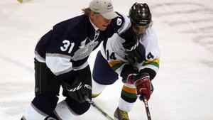 Ex-NHL player Mark Napier (L) fights for the puck against singer Sam Roberts (R) at the Juno Cup hockey game on March 30, 2007 in Prince Albert, Canada.