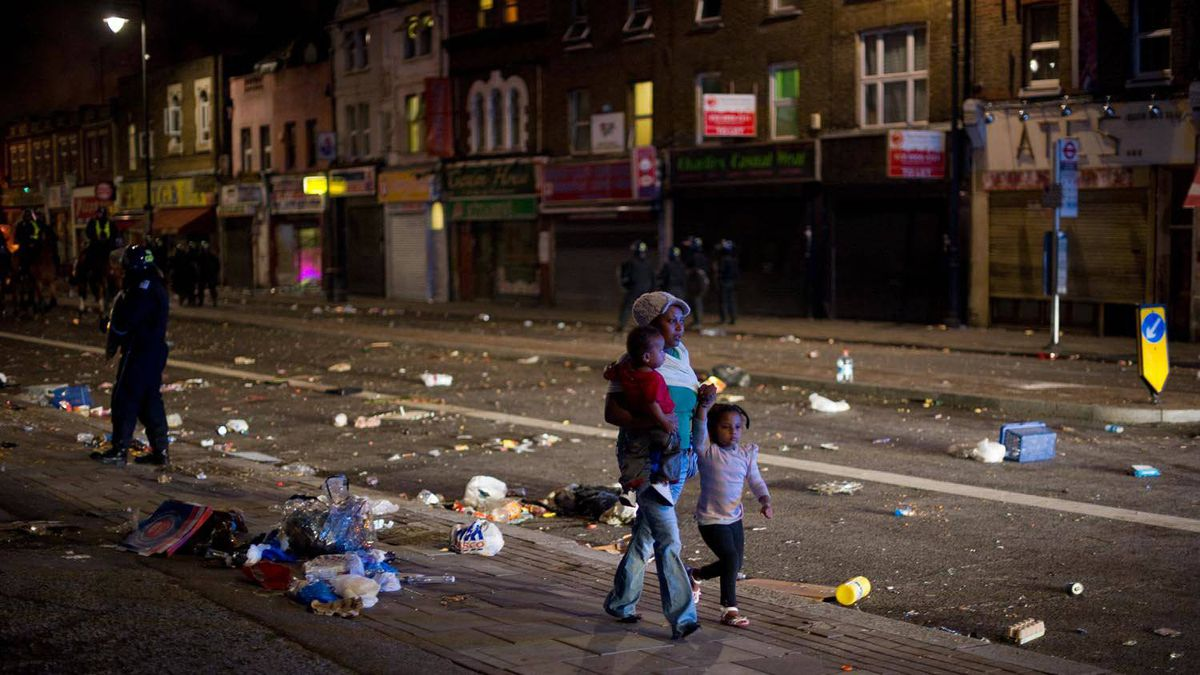 A woman walks through the debris with two children as riot police try to contain a large group of people on a main road in Tottenham, north London on August 6 2011.