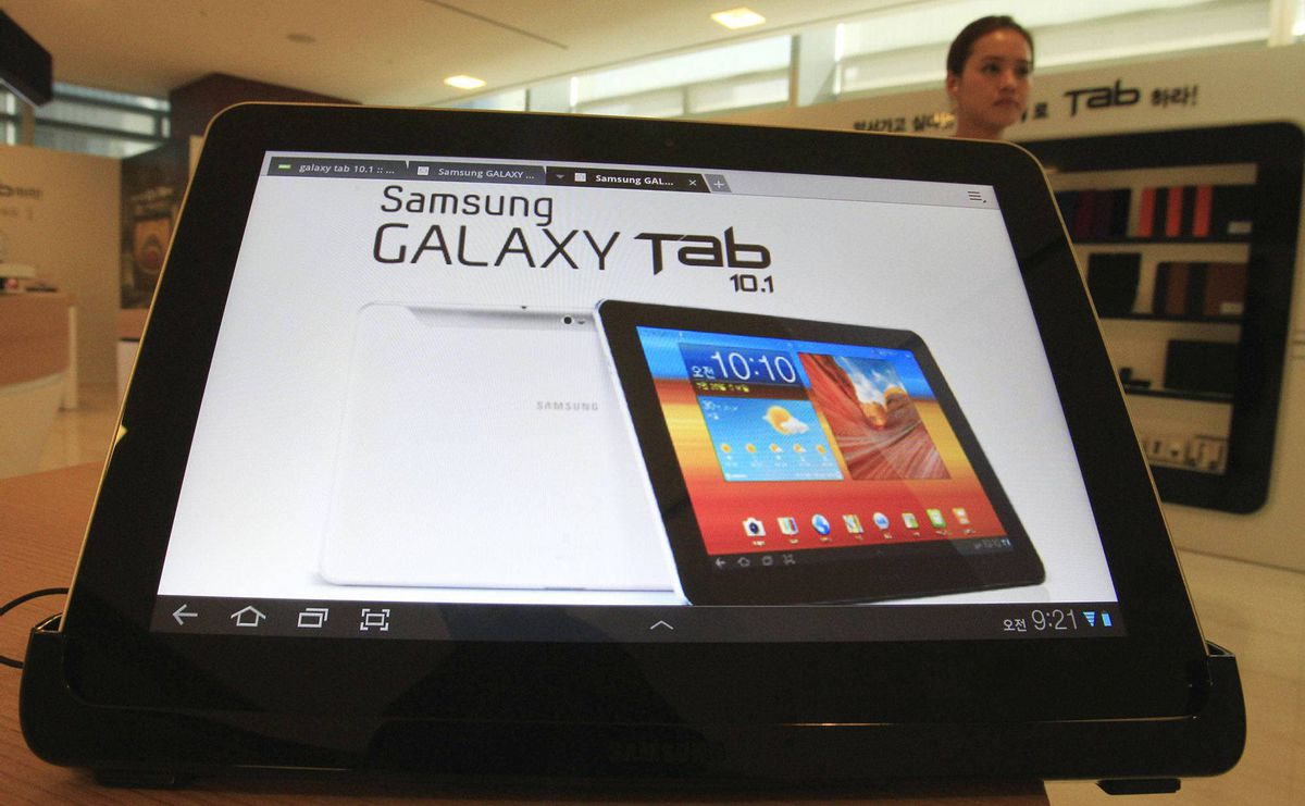 A woman walks near Samsung Electronics' new tablet Galaxy Tab 10.1 which features the 10.1-inch touch screen and runs on Android 3.1 during its unveiling ceremony in Seoul, South Korea, Wednesday, July 20, 2011.