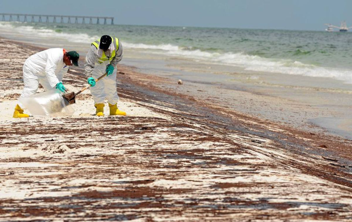 Crews work to clean up oil washed ashore at Pensacola Beach in Florida.