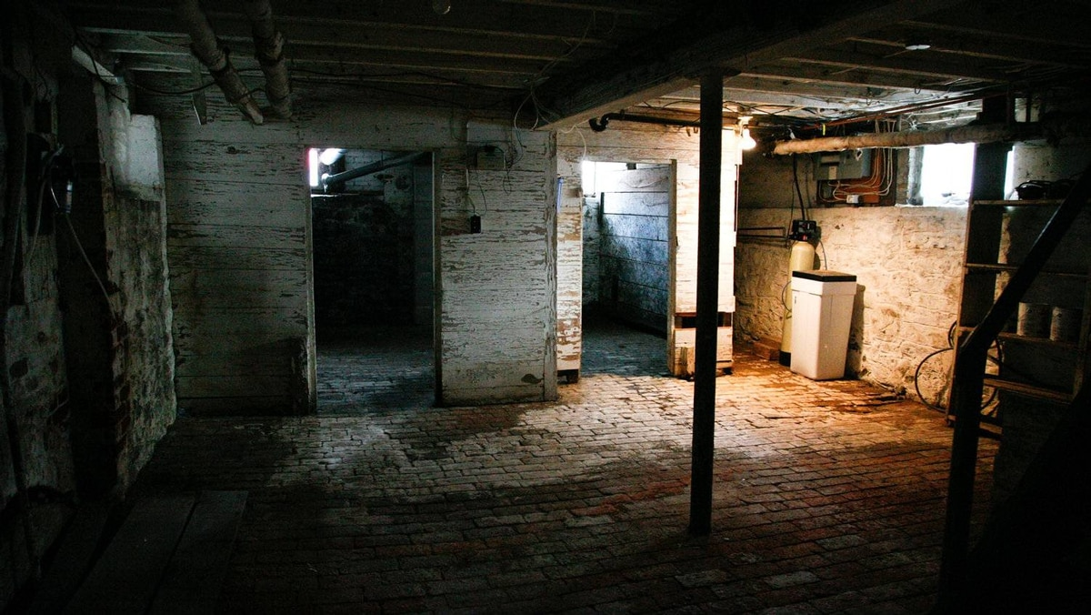 The basement is atests to the home's age, showing stome foundation walls and brick-paved floor.