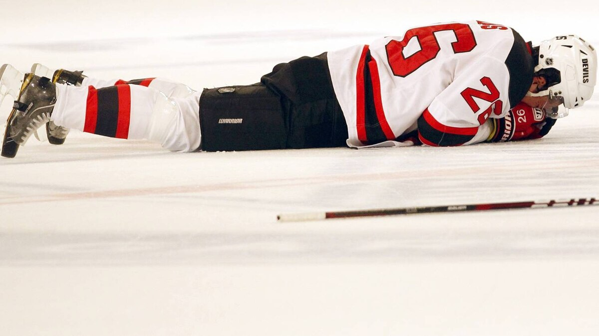 New Jersey Devils' Patrik Elias lies on the ice and holds his hand to his face after suffering an injury in the first period. REUTERS/Mike Segar