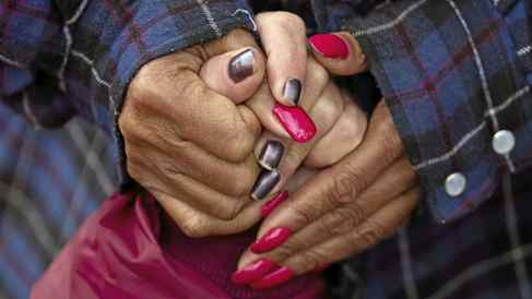 """Darlene Williams, 53, top, holds hands with Vicky Madison, bottom, outside of Rowan Helping Ministries, a homeless shelter in Salisbury, N.C., on Mon., Oct. 31, 2011. """"We're all family here,"""" Madison said. """"We hold each other up."""""""