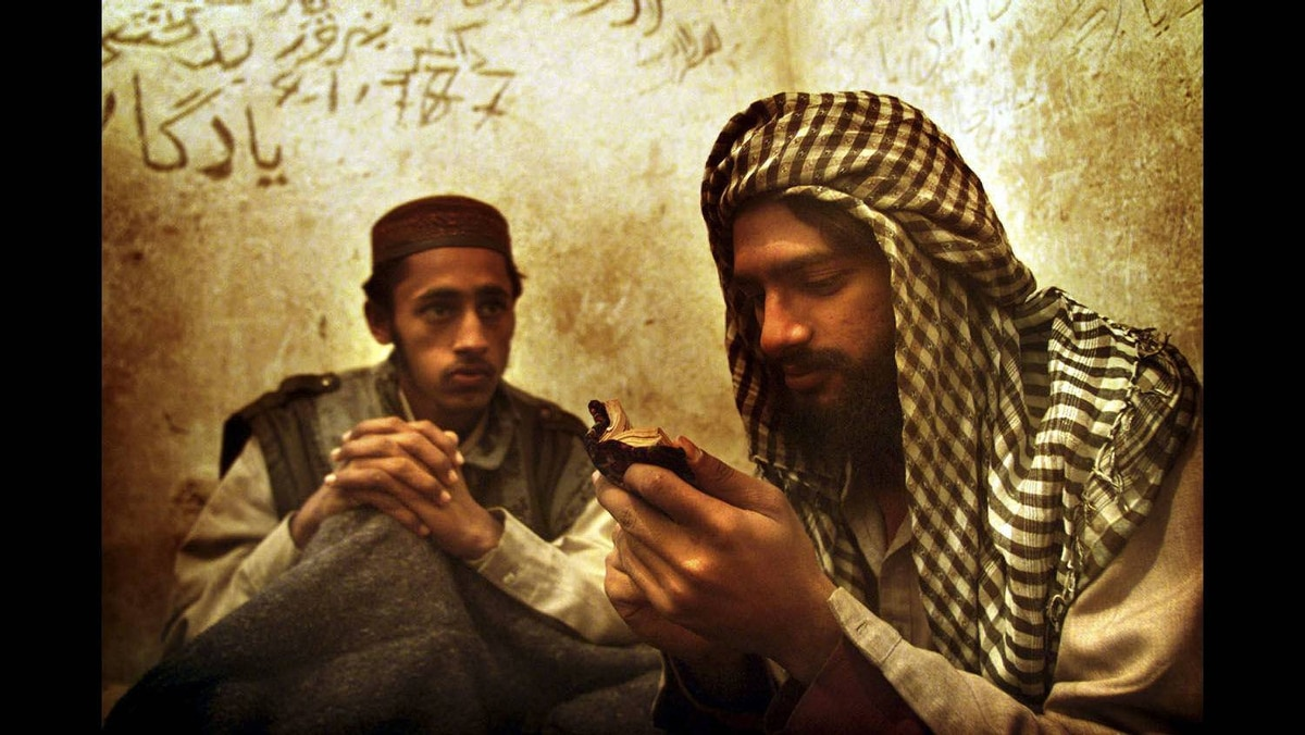Foreign members of the Taliban read the Koran in a military jail in Kabul, November 26, 2001.