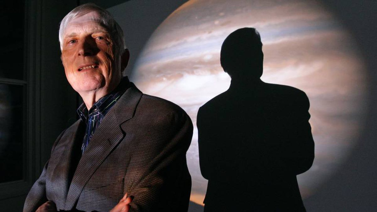 Professor emeritus Gordon Walker casts a shadow over a projected image of Jupiter, which has roughly the same mass as the exoplanet he discovered.