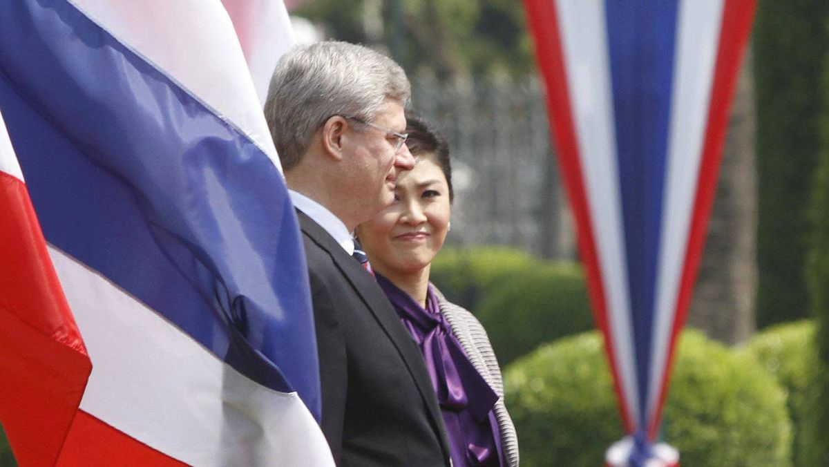 Prime Minister Stephen Harper, accompanied by Thailand's Prime Minister Yingluck Shinawatra, reviews an honour guard during a welcoming ceremony at the Government House in Bangkok on March 23, 2012.