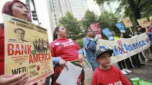 Members of the Ramirez family from Oakland (L-R) Emily, 15, Margarita and Marcus, 4, hold signs outside the Bank of America uptown headquarters before the Bank of America annual shareholder meeting in Charlotte, North Carolina May 9, 2012.